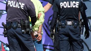 Two police officers arrest and handcuff homeless woman in Venice Beach, Los Angeles, California.